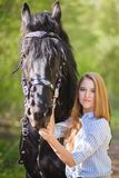 Beautiful girl stroking horse outside. Young beautiful girl stroking a horse outside Royalty Free Stock Image