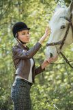 Beautiful girl stroking horse outside. Young beautiful girl stroking a horse outside Stock Photos