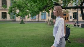 Young beautiful girl student is going near university in summer, studying concept, side view.  stock video footage