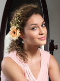 Young beautiful girl studio portrait. Young beautiful girl is smilimg. Flowers in her hair Royalty Free Stock Images