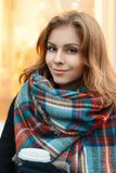 Young beautiful girl in stylish knitted scarf and black coat dri Stock Image