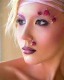 Young beautiful girl, stylish purple makeup and roses on face Stock Images