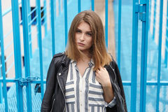 Young beautiful girl in stylish streetwear black leather jacket long striped dress white sneakers and with a fashionable bag posin. G against blue painted metal Royalty Free Stock Image
