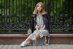 Young beautiful girl in stylish streetwear black leather jacket long striped dress white sneakers and with a fashionable bag sitti. Ng in summer city park Royalty Free Stock Images