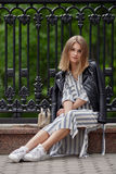 Young beautiful girl in stylish streetwear black leather jacket long striped dress white sneakers and with a fashionable bag sitti Royalty Free Stock Images