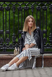 Young beautiful girl in stylish streetwear black leather jacket long striped dress white sneakers and with a fashionable bag sitti Stock Images
