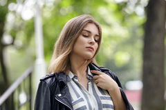 Young beautiful girl in stylish streetwear black leather jacket long striped dress white sneakers and with a fashionable bag strol Stock Image