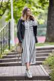 Young beautiful girl in stylish streetwear black leather jacket long striped dress white sneakers and with a fashionable bag strol. Ling in summer city park Stock Photography