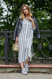 Young beautiful girl in stylish streetwear black leather jacket long striped dress white sneakers and with a fashionable bag strol. Ling in summer city park Stock Photo