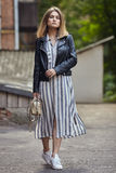 Young beautiful girl in stylish streetwear black leather jacket long striped dress white sneakers and with a fashionable bag strol. Ling in summer city park Royalty Free Stock Photography