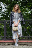 Young beautiful girl in stylish streetwear black leather jacket long striped dress white sneakers and with a fashionable bag strol. Ling in summer city park Stock Image