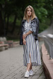 Young beautiful girl in stylish streetwear black leather jacket long striped dress white sneakers and with a fashionable bag strol. Ling in summer city park Royalty Free Stock Image