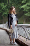 Young beautiful girl in stylish streetwear black leather jacket long striped dress white sneakers and with a fashionable bag strol Royalty Free Stock Images