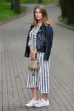 Young beautiful girl in stylish streetwear black leather jacket long striped dress white sneakers and with a fashionable bag strol. Ling in summer city park Stock Photos