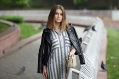 Young beautiful girl in stylish streetwear black leather jacket long striped dress white sneakers and with a fashionable bag strol Royalty Free Stock Image