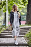 Young beautiful girl in stylish streetwear black leather jacket long striped dress white sneakers and with a fashionable bag strol Stock Images