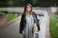 Young beautiful girl in stylish streetwear black leather jacket long striped dress white sneakers and with a fashionable bag strol Stock Photography