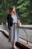 Young beautiful girl in stylish streetwear black leather jacket long striped dress white sneakers and with a fashionable bag strol. Ling in summer city park Royalty Free Stock Images