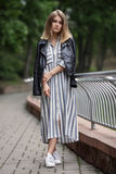 Young beautiful girl in stylish streetwear black leather jacket long striped dress white sneakers and with a fashionable bag strol Stock Photos