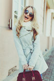 Young beautiful girl in stylish sunglasses and with a fashionable bag city streets. Royalty Free Stock Photos