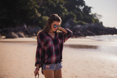 Young beautiful girl in stylish sunglasses and with a fashionable bag at sunset walking on a beach Royalty Free Stock Images