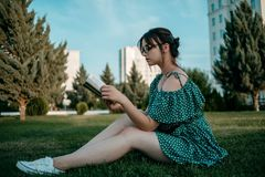 Young beautiful girl in the summer short dress reads a book sitting on the grass.  stock photos
