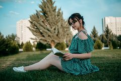 Young beautiful girl in the summer short dress reads a book sitting on the grass.  royalty free stock images