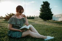 Young beautiful girl in the summer short dress reads a book sitting on the grass.  stock image