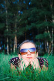 Young beautiful girl in sun glasses. Lying in green grass Stock Photos
