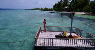 V08111 young beautiful girl sunbathing on pontoon with drone aerial flying view in clear blue sea and sunshine Stock Photo