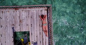 V08145 young beautiful girl sunbathing on pontoon with drone aerial flying view in clear blue sea and sunshine Stock Photography