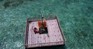 V08114 young beautiful girl sunbathing on pontoon with drone aerial flying view in clear blue sea and sunshine Stock Photos
