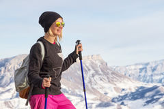 Young beautiful girl in sunglasses with Nordic poles in the sunset light on the background of the Caucasian ridge. And rock Royalty Free Stock Images