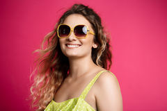 Young beautiful girl in sunglasses smiling over pink background. Royalty Free Stock Images