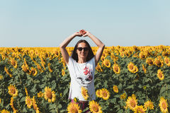 Young Beautiful Girl Standing In Sunflowers And Raising Hands Up. Freedom Lifestyle Journey Concept royalty free stock photos