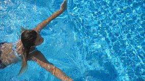 Young beautiful girl swimming in pool. Brunette relaxing in clear warm water on sunny day. Top view Close up Slow motion stock footage