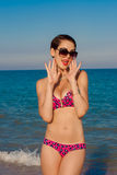 Young beautiful girl in swimsuit at the beach. Smiling Royalty Free Stock Image
