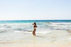 Young beautiful  girl in swimsuit bikini posing on beach, fashion model, fitness figure. Young beautiful  girl in white swimsuit bikini posing on beach in Stock Image