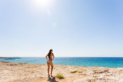 Young beautiful  girl in swimsuit bikini posing on beach, fashion model, fitness figure. Young beautiful  girl in white swimsuit bikini posing on beach in Stock Photos