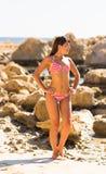 Young beautiful  girl in swimsuit bikini posing on beach, fashion model, fitness figure. Young beautiful  girl in white swimsuit bikini posing on beach in Royalty Free Stock Image