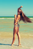 Young beautiful girl in swimsuit and sunglasses at the beach Royalty Free Stock Photo