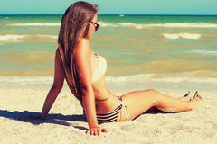 Young beautiful girl in swimsuit and sunglasses at the beach Royalty Free Stock Images
