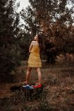 Young beautiful girl takes off a yellow dress to dress clothes from a vintage suitcase.  stock photography