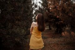 Young beautiful girl takes off a yellow dress to dress clothes from a vintage suitcase.  royalty free stock photography