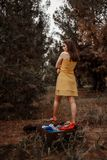 Young beautiful girl takes off a yellow dress to dress clothes from a vintage suitcase.  royalty free stock photo