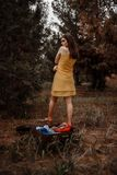 Young beautiful girl takes off a yellow dress to dress clothes from a vintage suitcase.  stock photos