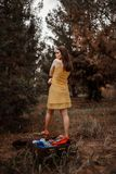 Young beautiful girl takes off a yellow dress to dress clothes from a vintage suitcase.  stock images