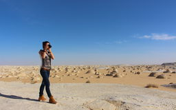 Young beautiful girl takes a picture in the middle of the amazing White desert close to Farafra oasis in Egypt Stock Photos
