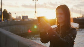 Young beautiful girl taking selfie on the background of the bridge in the bright rays of the setting sun. 4K stock video footage