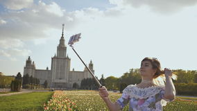Young beautiful girl taking selfie stick picture happy on sunny day stock footage